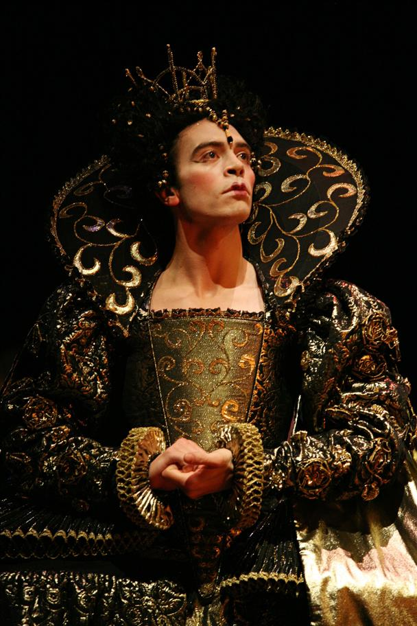 A man in an ornate black and gold gown, with a high collar and jewelled crown.