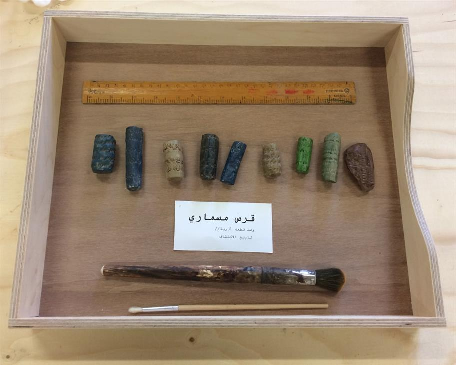 A museum drawer containing some coloured stone fragments and various utensils.