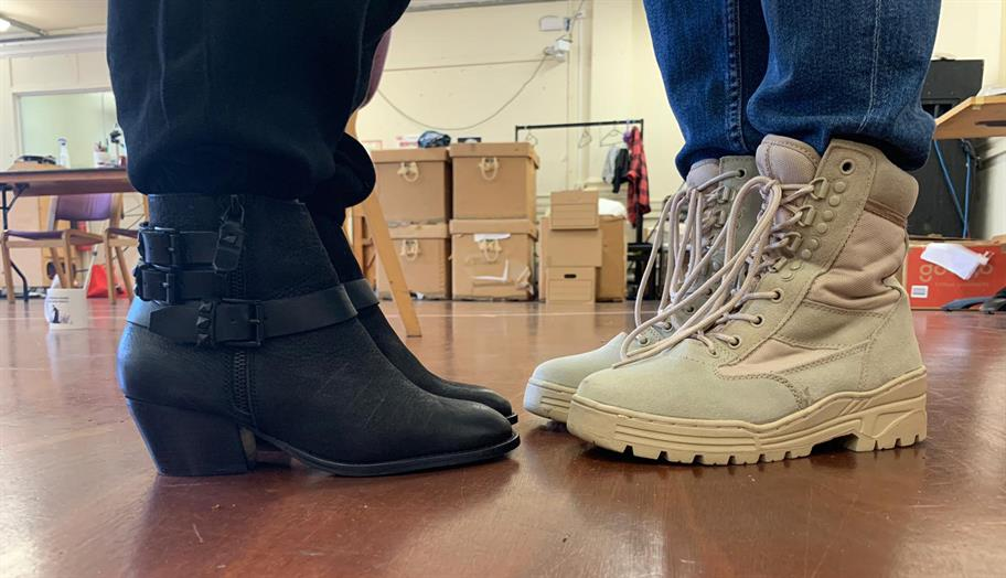 A pair of black wedge heel boots pointing towards a pair of white walking boots.