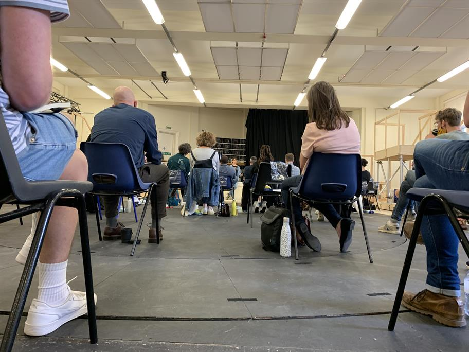 Sitting socially distanced in the rehearsal room.