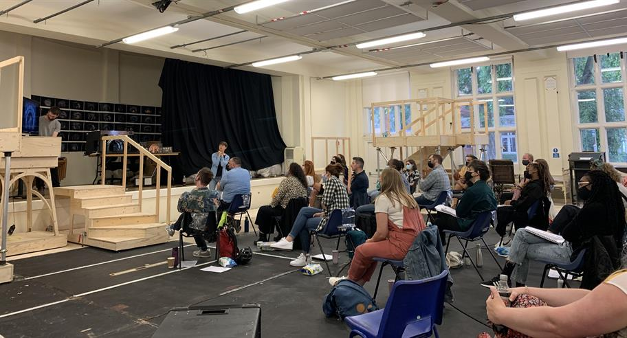 The cast watch a presentation in the rehearsal room.