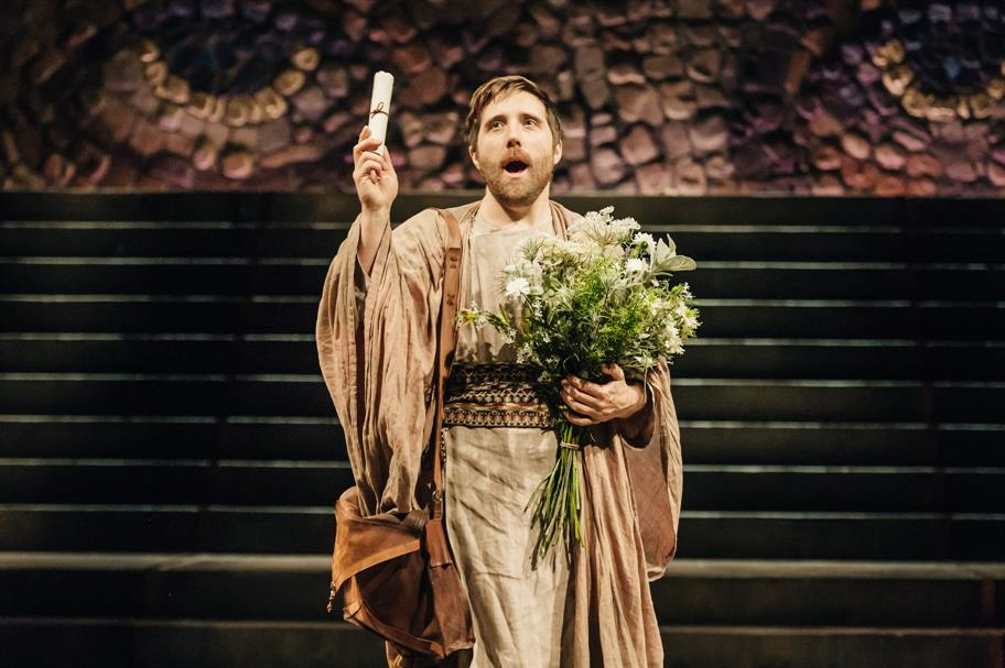 A man in Roman robes holds a scroll and bouquet of flowers.