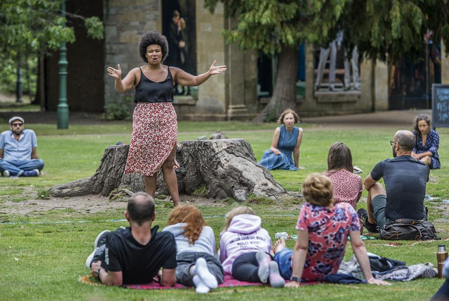 A woman performs to an audience outdoors.
