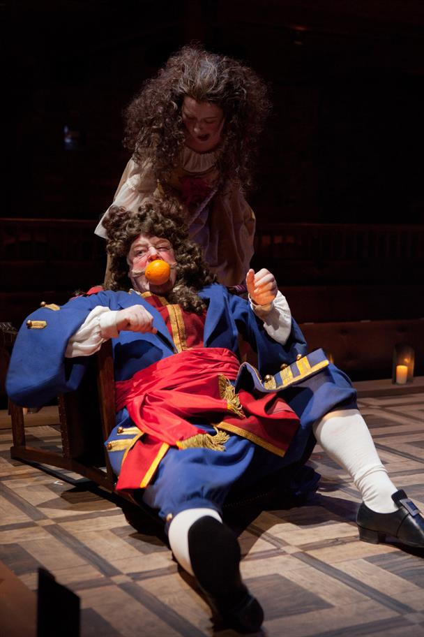 A woman stands over a man who lies on the floor with an orange wedged in his mouth.