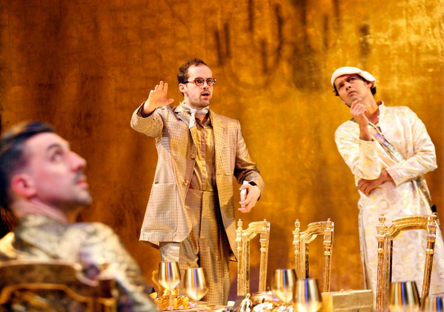 Three men in white and gold around a gold-laden table and a gold background.