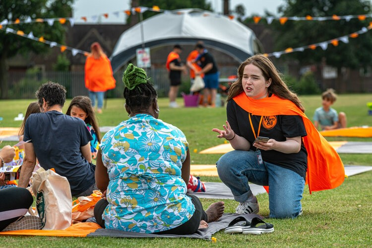 A woman in an orange cape talks to someone sat on a picnic blanket.