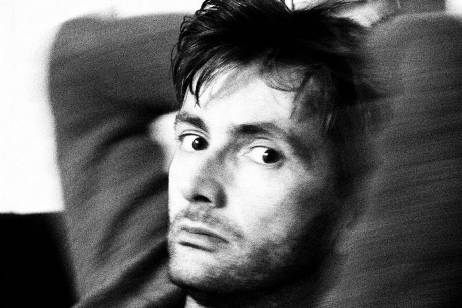 Headshot of David Tennant in black and white with his hands behind his head