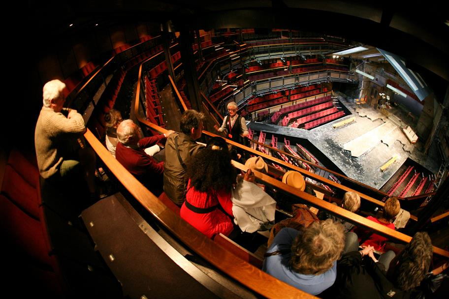 A group of visitors listening to a tour guide in the Royal Shakespeare Theatre