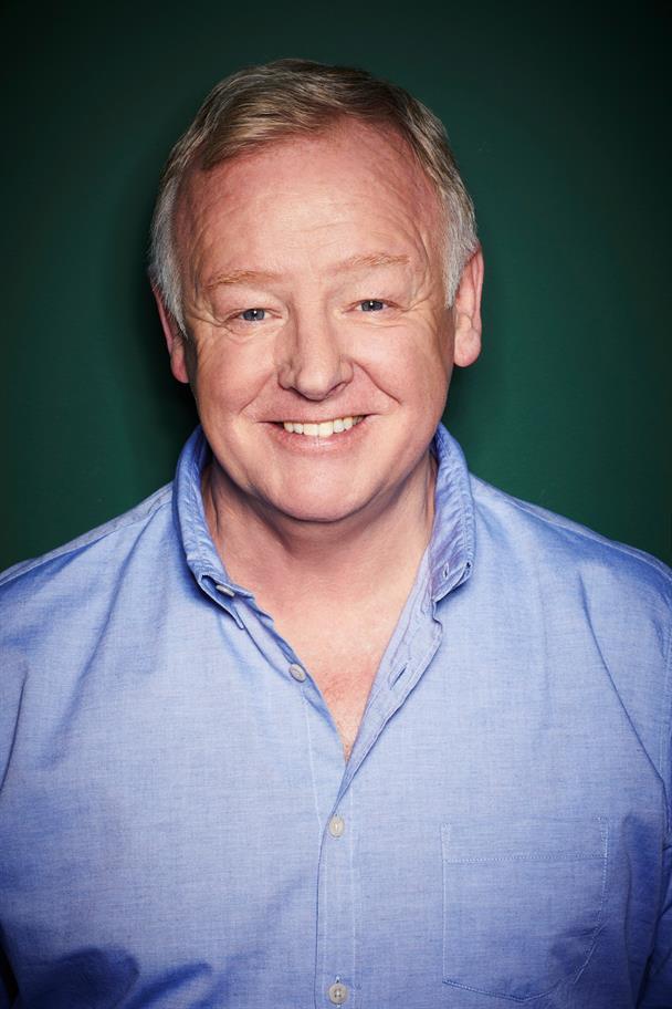 Les Dennis in a blue shirt, smiling