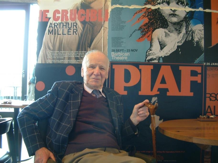 Frank Benson wearing a dark jacket, cardigan and a tie, sitting against a wall full of old theatre posters