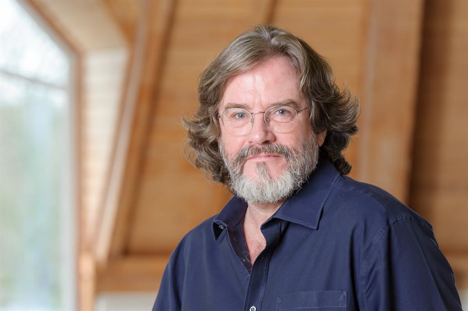 Gregory Doran in a wood panelled room wearing a dark blue shirt
