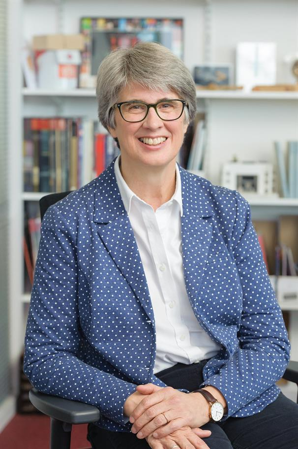 Catherine Mallyon seated in an office, with bookshelves behind her, wearing a blue polka dot jacket