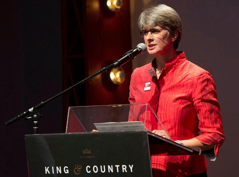 Catherine Mallyon in a red shirt speaking into a microphone, standing at a lectern that says 'King and Country'