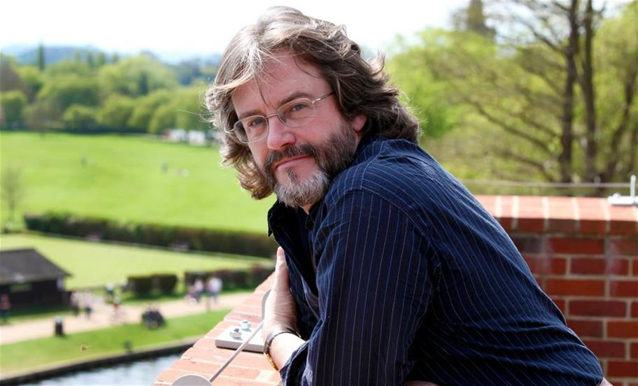 Gregory Doran in a dark blue shirt leaning on the balcony