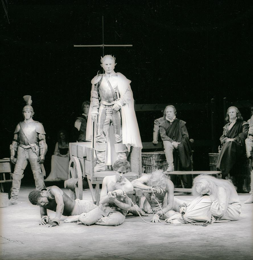 Four prisoners lie hurt in the foreground while Titus stands behind them on a cart wearing armour