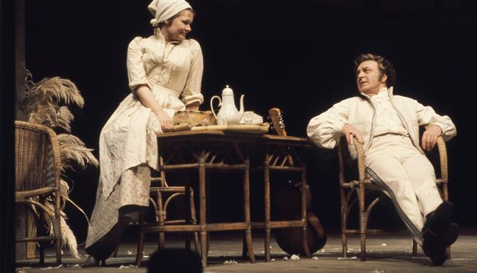 Beatrice sits on a table smiling at Benedick who is seated with crossed legs