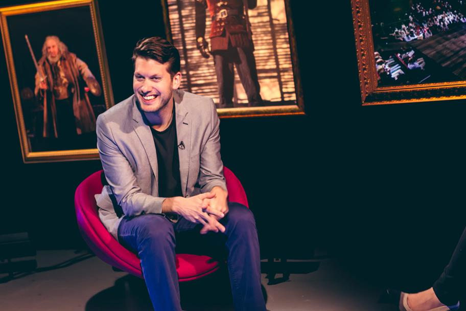 Owen Horsley smiling seated in a red chair in front of framed pictures from Henry IV
