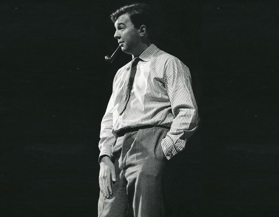 Black and white photo of Peter Hall in 1962 smoking a pipe with his left hand in his pocket