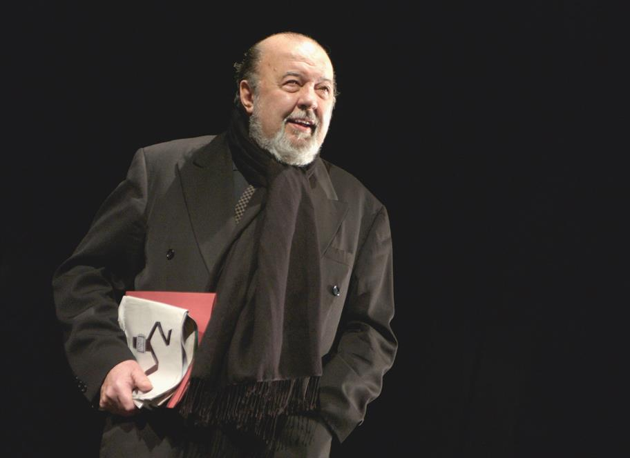 Sir Peter Hall in a black suit and black scarf with papers tucked under his arm