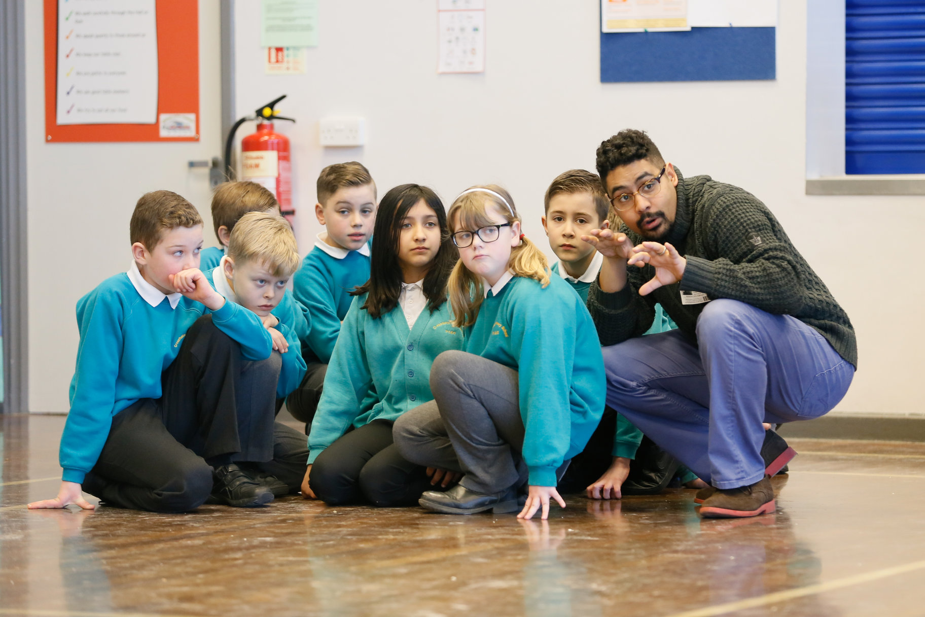 A man crouching down with a group of schoolchildren