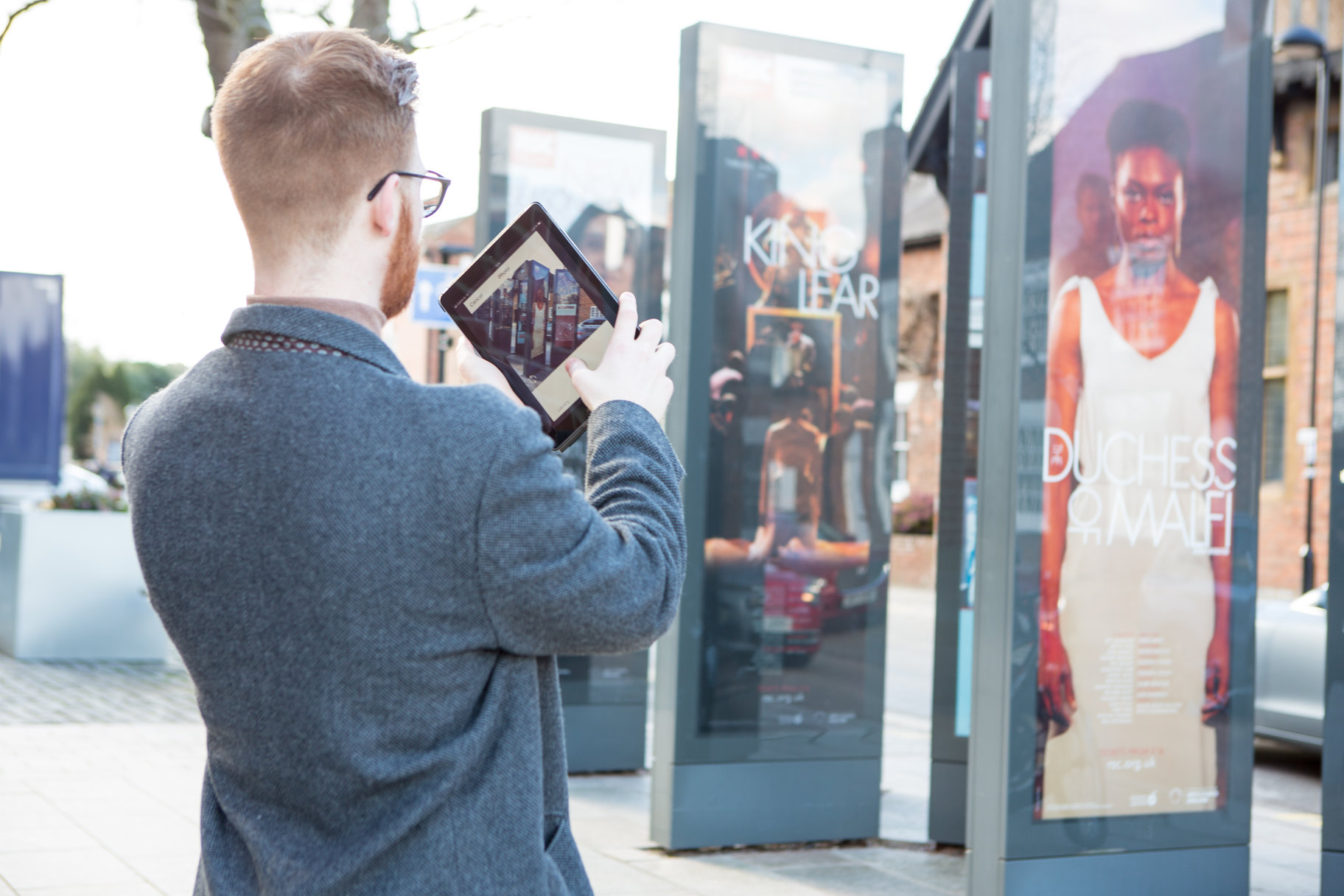 man outside the theatre taking photos on a tablet