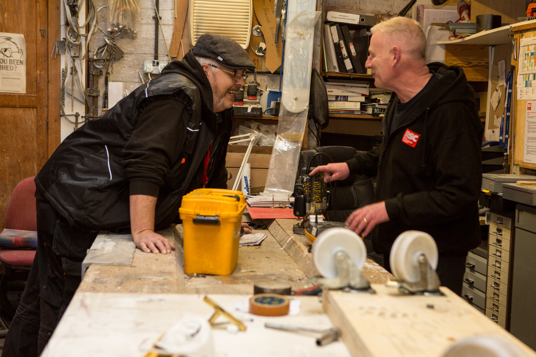two men in a workshop talking and laughing