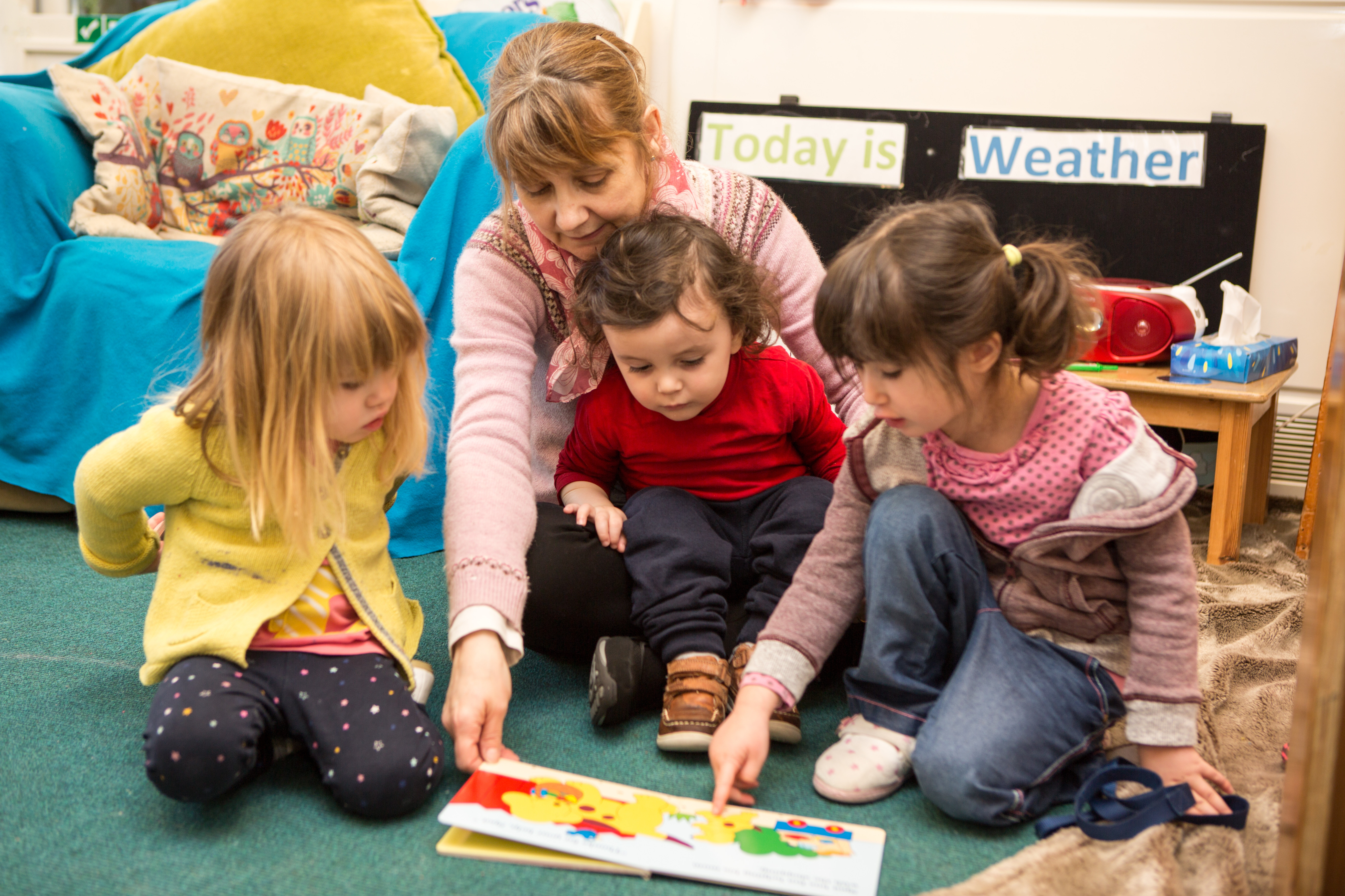 Three small children sitting on the floor pointing and talking about a book with their teacher