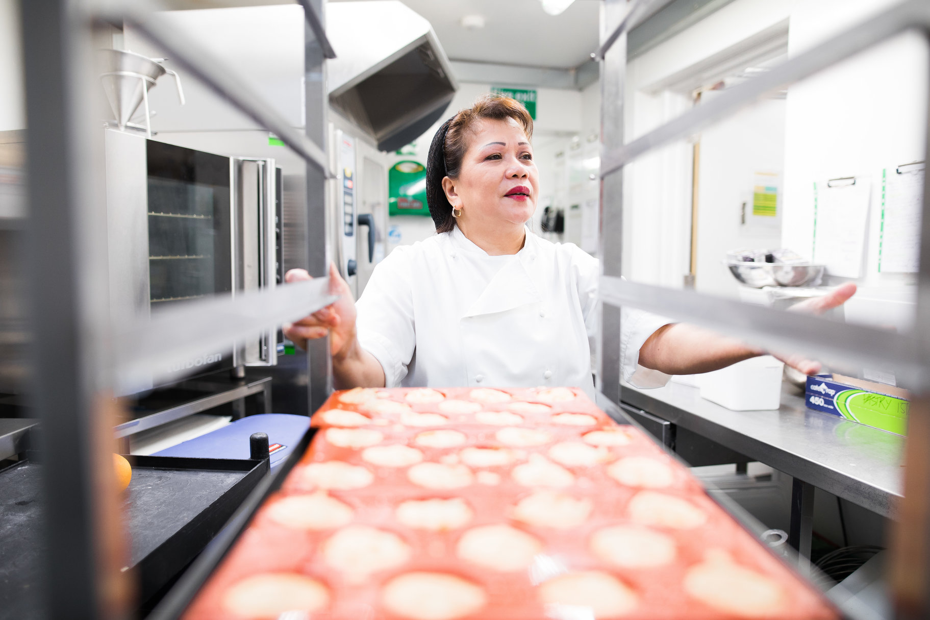 woman dressed in chef's whites taking pastries out of an industrial oven