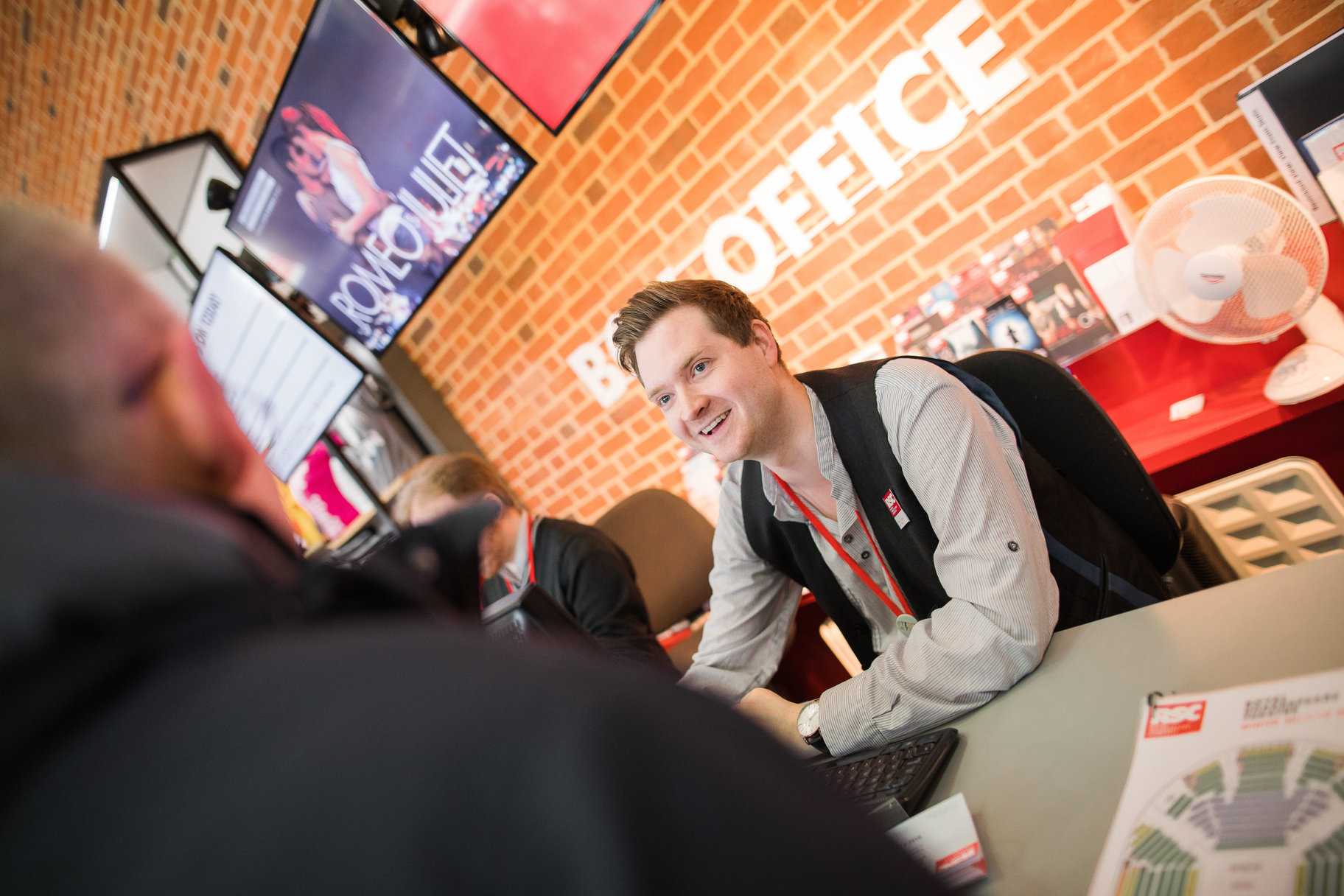 Smiling man in waistcoat helping someone at Box Office