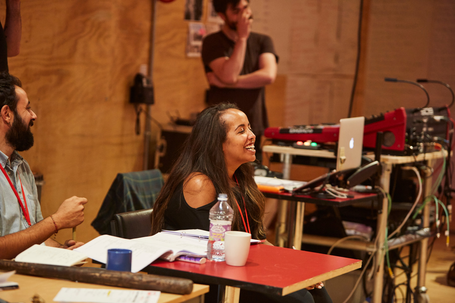 Young woman sitting behind a desk in a rehearsal room and laughing