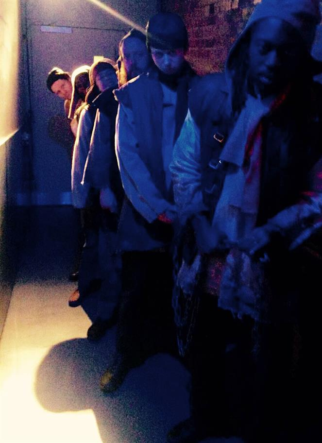 The cast of Don Quixote dressed as galley slaves waiting in a dark corridor to go on stage