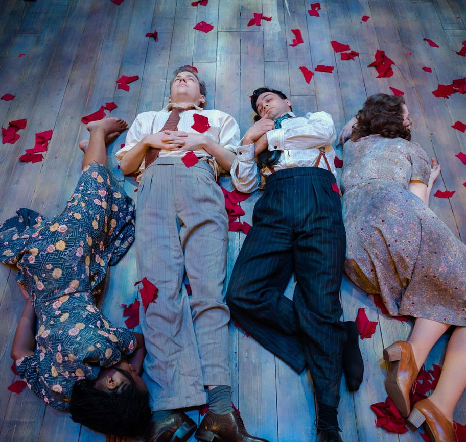 Four lovers from A Midsummer Night's Dream in 1940s clothes sleeping on the floor, on top of scattered red fabric