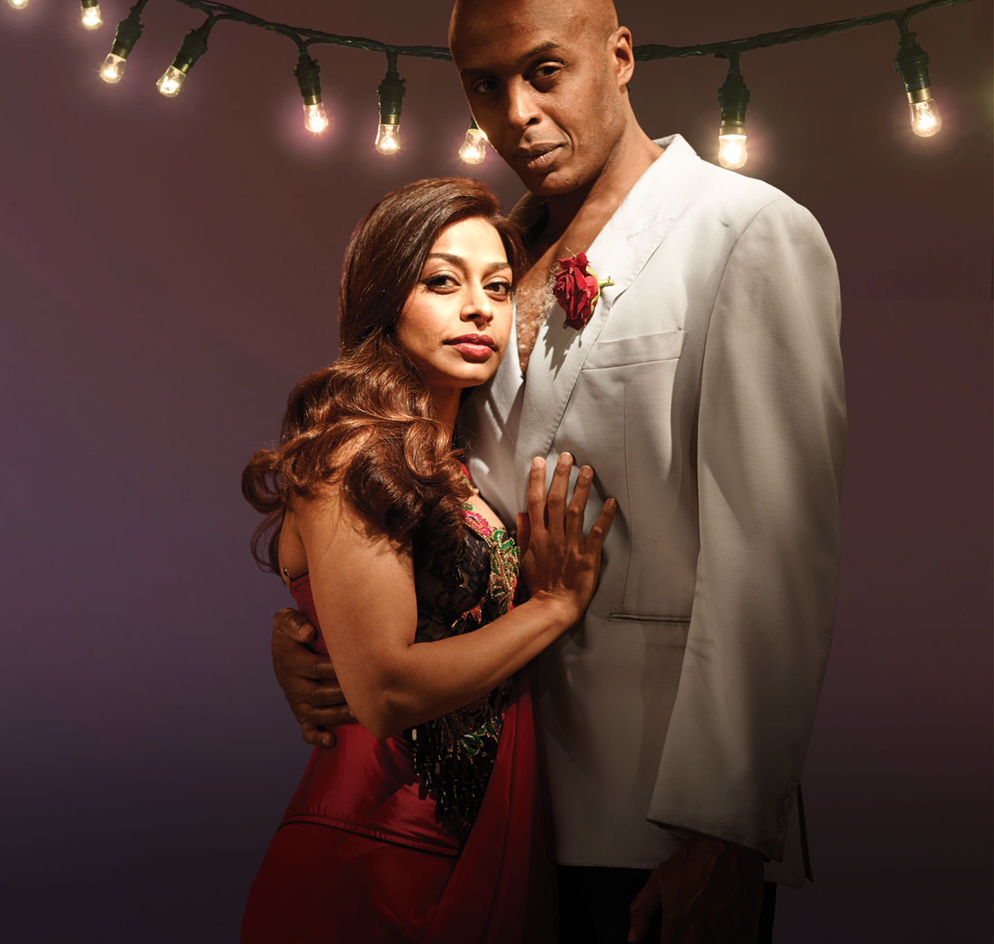 Ayesha Dharker in a red dress and Chu Omambala in a white suit jacket with no shirt, embrace and look at the camera