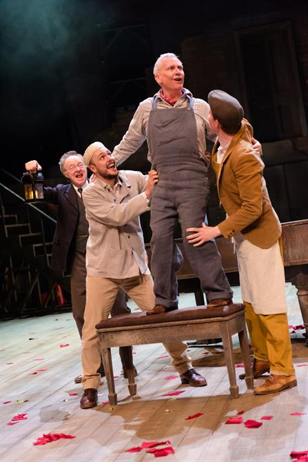 A man stands on a piano chair, supported by other men