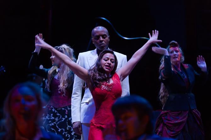 A woman in a red dress dances in front of a man in a white suit