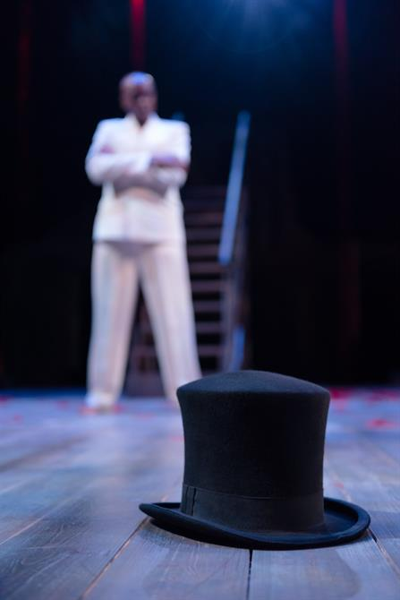 A man in a white suit stands in the background of a hat on the floor