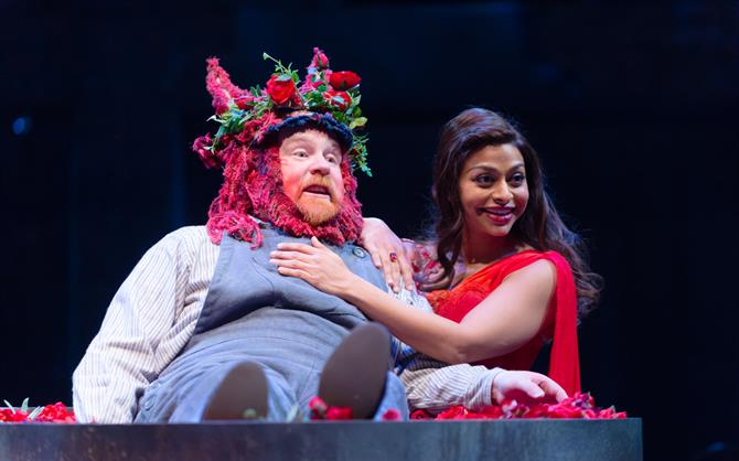 A man in a pink and flowery headdress lies next to a woman in a red dress