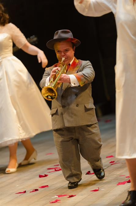 A man plays a trumpet and dances