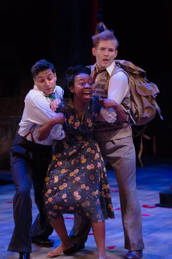 Two men hold back a screaming woman by her arms
