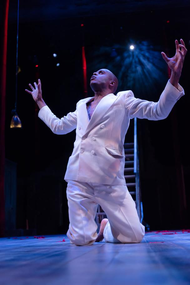 CHU OMAMABALA as Oberon in a white suit on his knees with arms upraised