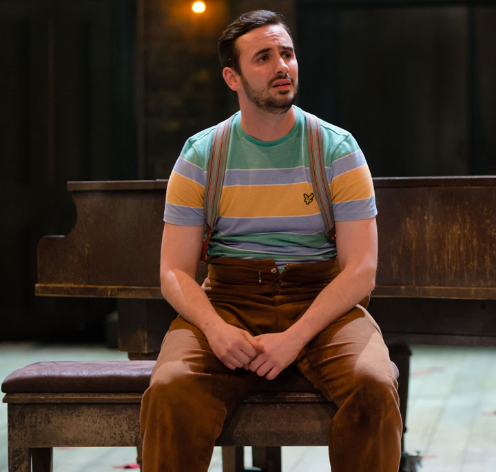Dominic Skinner as Flute in Dream, wearing a bright striped t-shirt and suspended brown trousers, sitting on a piano stool