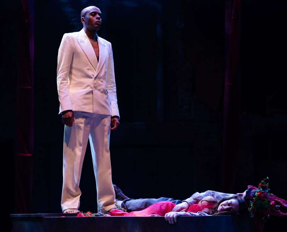 Chu Ombalala as Oberon in a white suit standing over Titania (Ayesha Dharker)