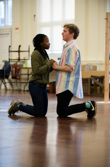 Mercy Ojelade and Jack Holden kneeling down in rehearsal holding hands