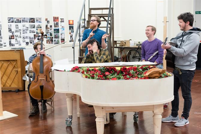 A group of actors sing around a piano full of red roses