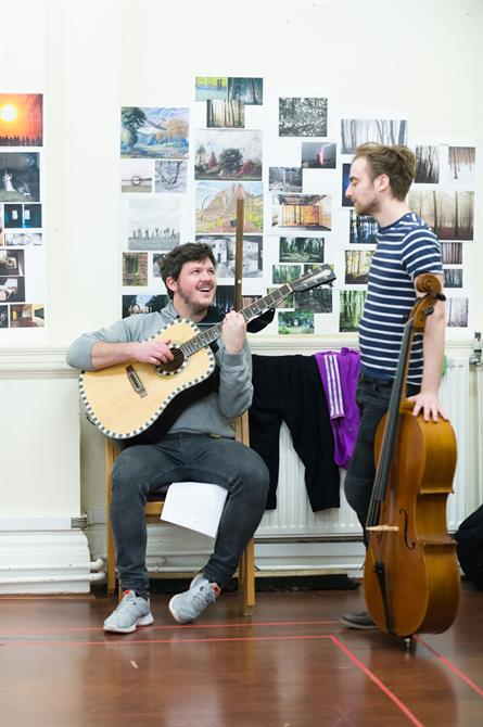 Two men laughing and playing their instruments in rehearsal: one has a guitar, the other a 'cello