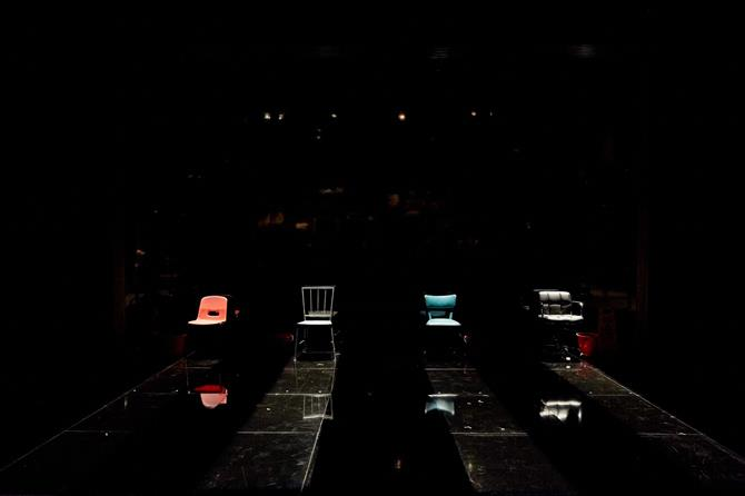 four empty chairs in row on a black stage with shafts of light shining on them
