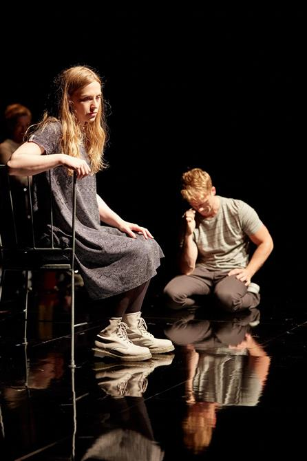 a woman sits on a chair looking sadly to the side, while a man kneels in front of her with his head down and hand by his face