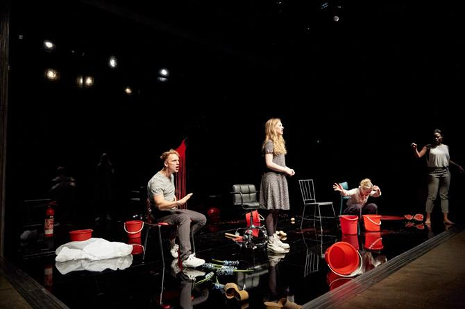 a man sits on a chair, a woman stands nearby, another woman is crouched next to two red buckets and a third woman stands in the distance pointin. There is a lot of debris on the the stage.
