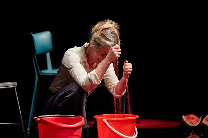 a woman crouches onstage with two red buckets in front of her. Grains of red sand fall from between her clenched fists.