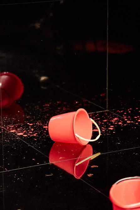 a red bucket lying on it's side on stage with red liquid splattered around